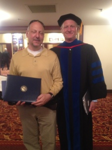Jim Gallagher graduates with honors with an MBA from Marquette.  Pictured here with the Dean of the Graduate School of Management